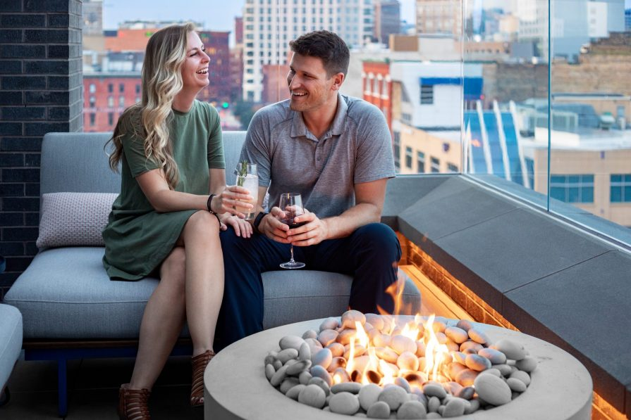 Couple with drinks at a fire pit