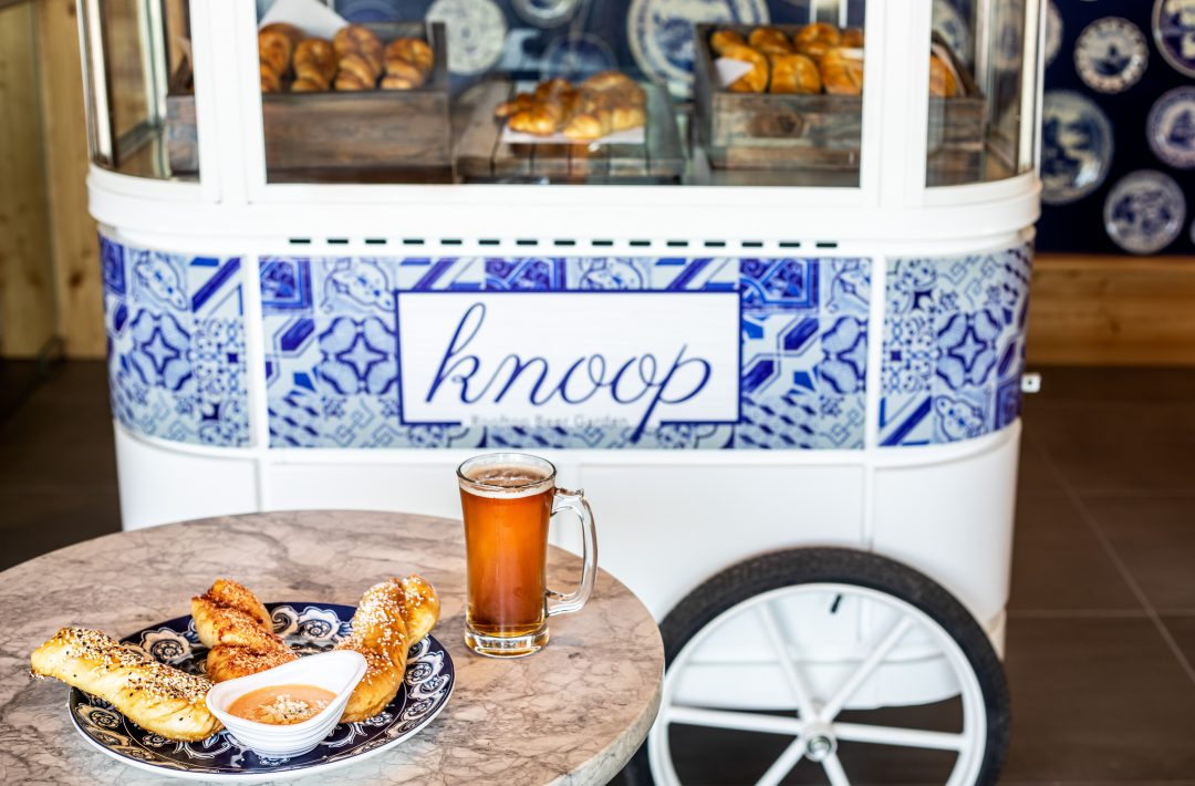 Table with bread and beer in front of cart with Knoop logo